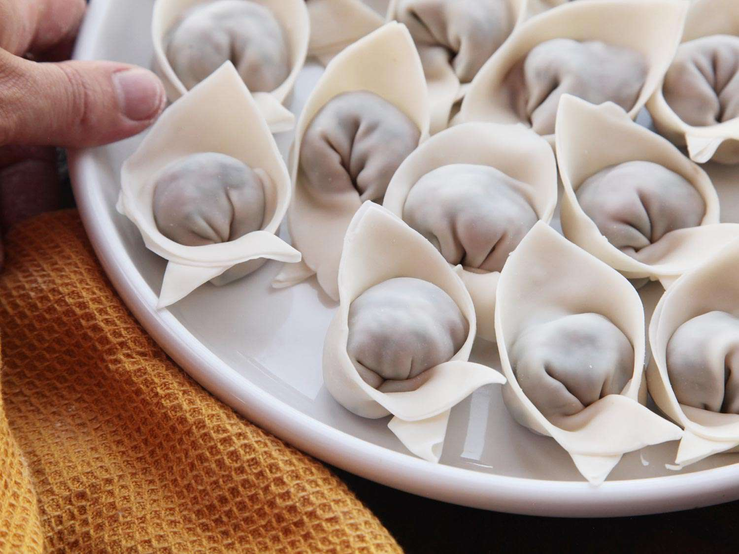 Transferring finished wontons onto a plate