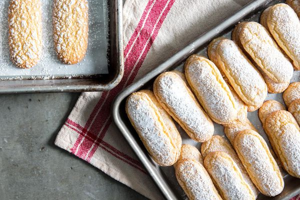 Two parchment-lined sheet pans with one-bowl ladyfinger cookies.