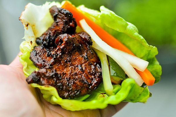 Daeji Bulgogi wrapped in a lettuce cup with pickled daikon radish, carrots, and cucumber.