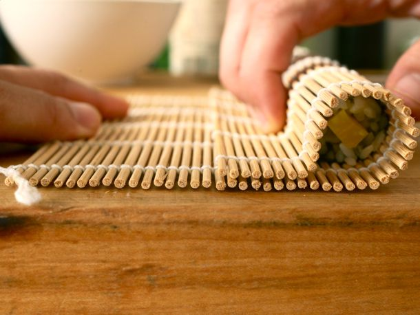 A sushi mat being used to roll sushi.