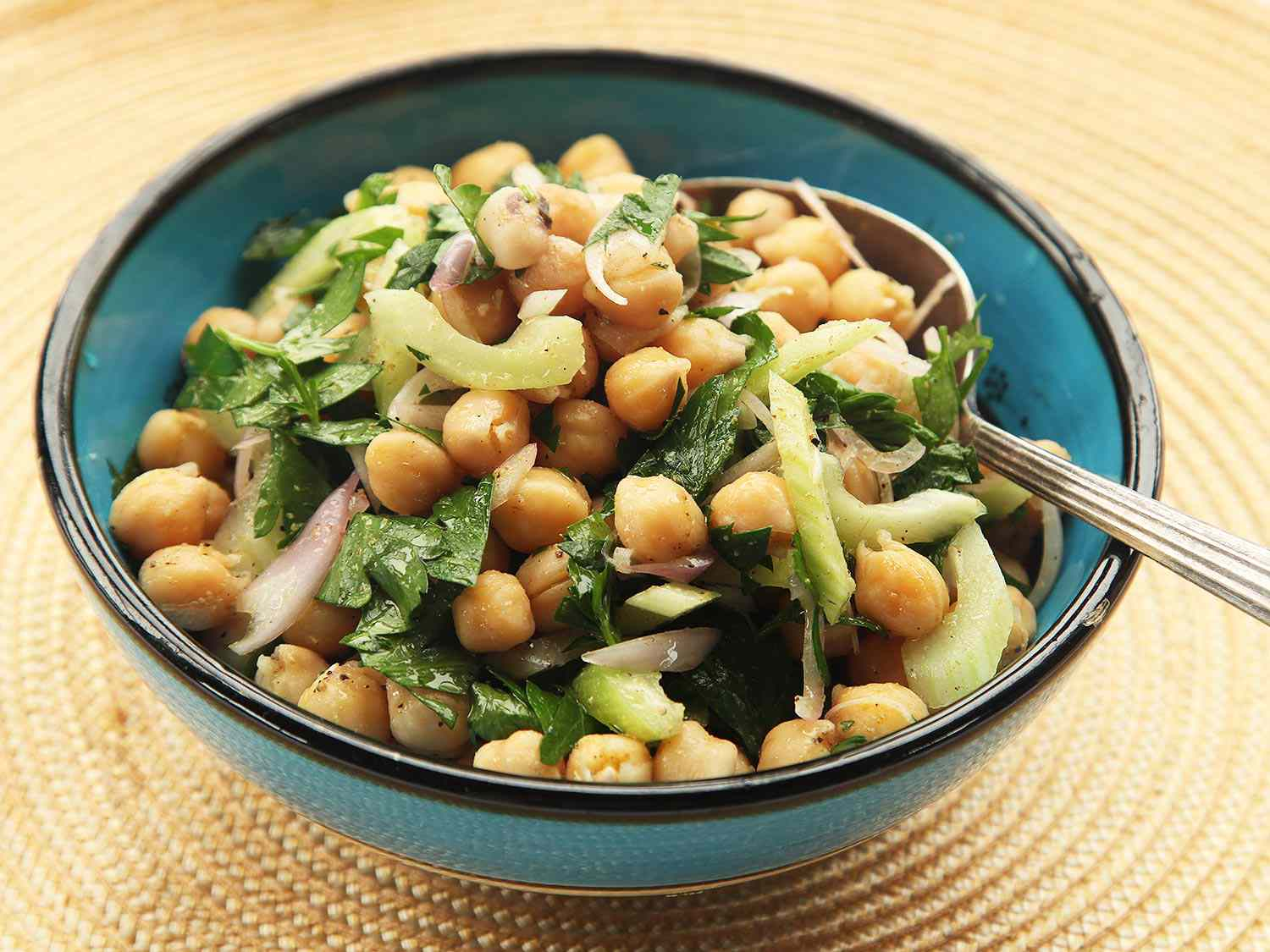 Chickpea and cumin salad in a blue and black bowl.