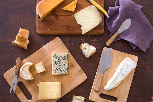 Three cheese boards with an assortment of cheeses and four cheese knives.