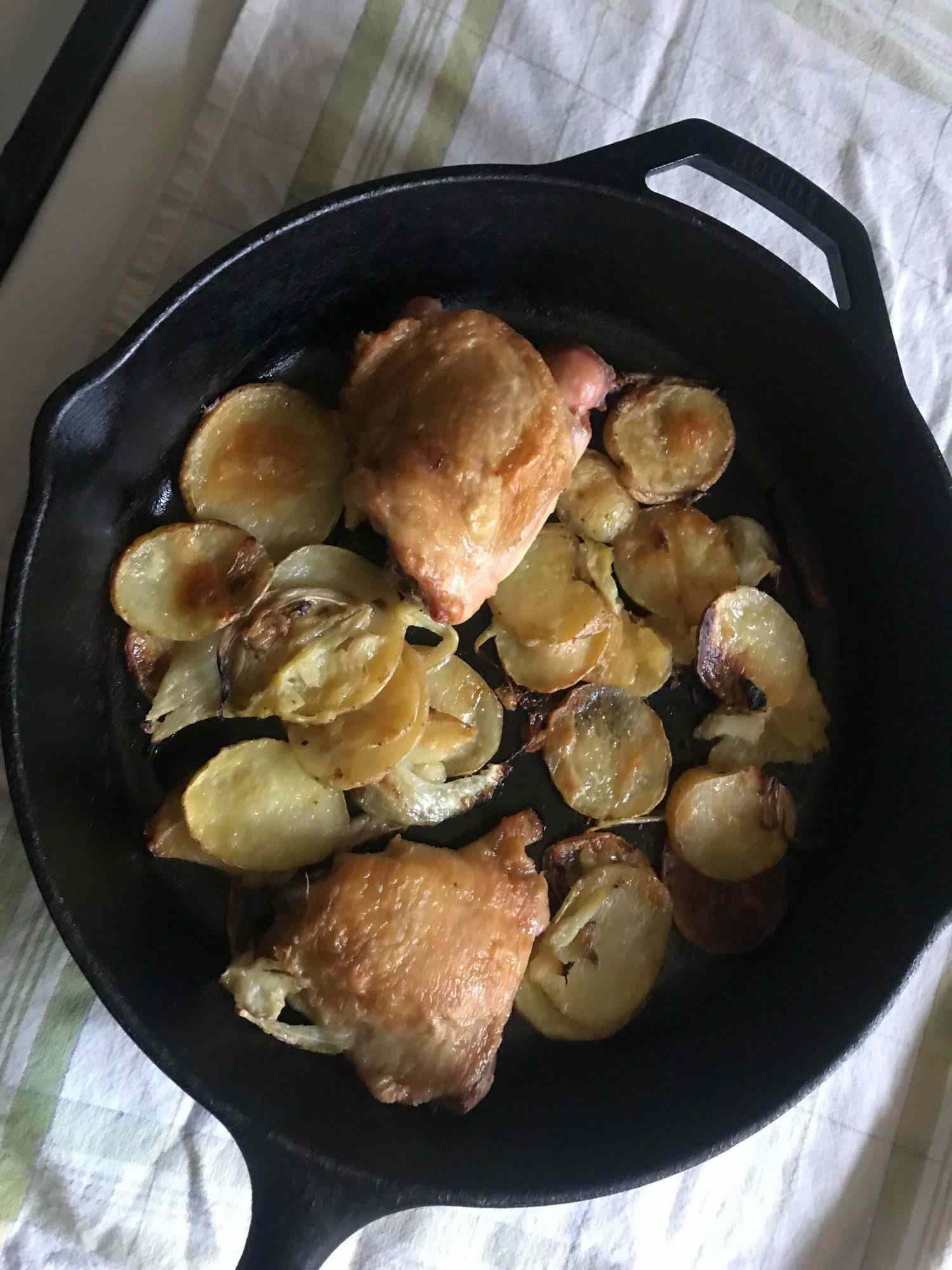 Chicken thighs and sliced potatoes and fennel in a cast iron pan