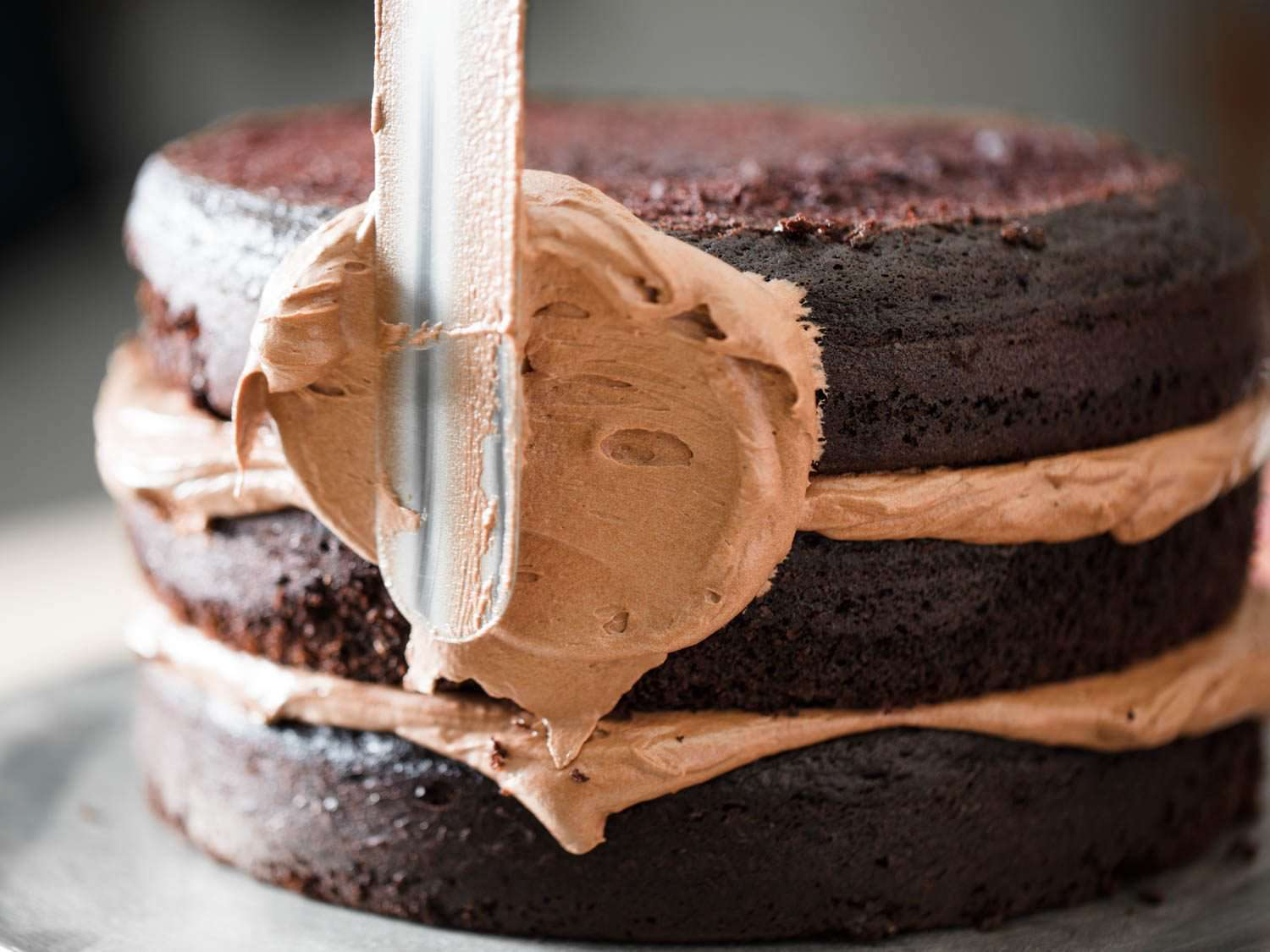 Frosting sides of three-layer Devil's food cake with chocolate Swiss buttercream.