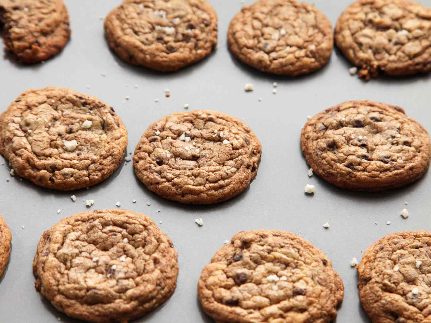 An array of chocolate chip cookies on a grey background.