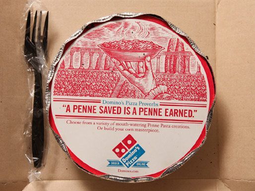 A delivery container from Domino's - a round aluminum dish with a cardboard top and aluminum edges crimped over it. A plastic fork is also in the box.