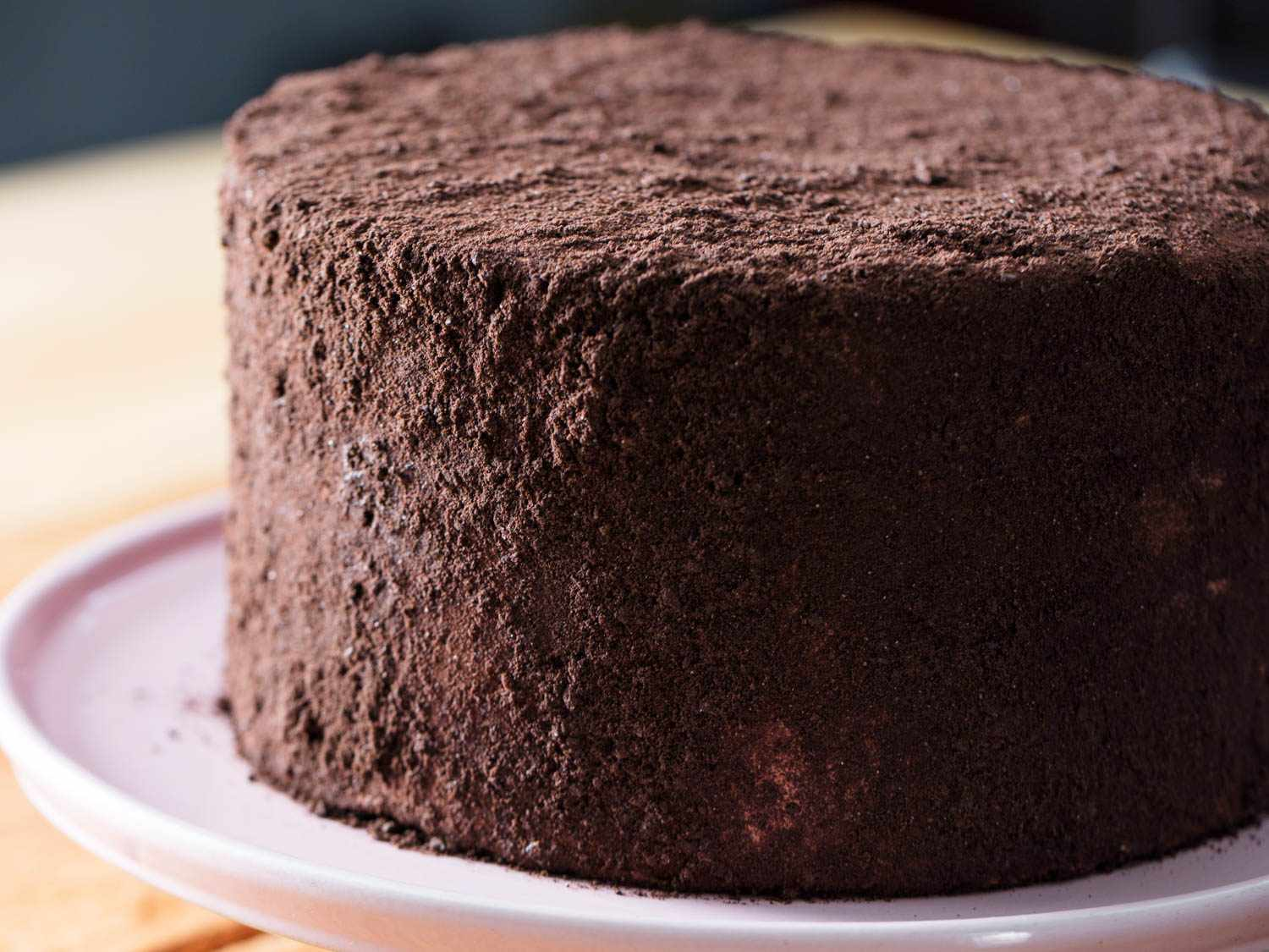 Oreo cookie-crumb coated three-layer Devil's food cake on pink cake stand.