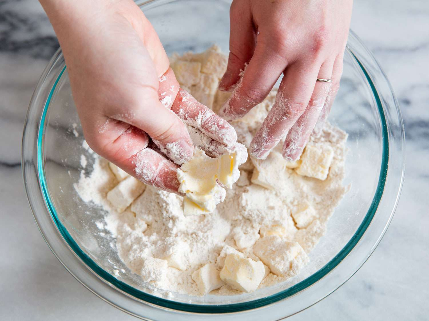 Hands working with a glass bowl of flour and butter, smashing flour-coated butter cubes flat