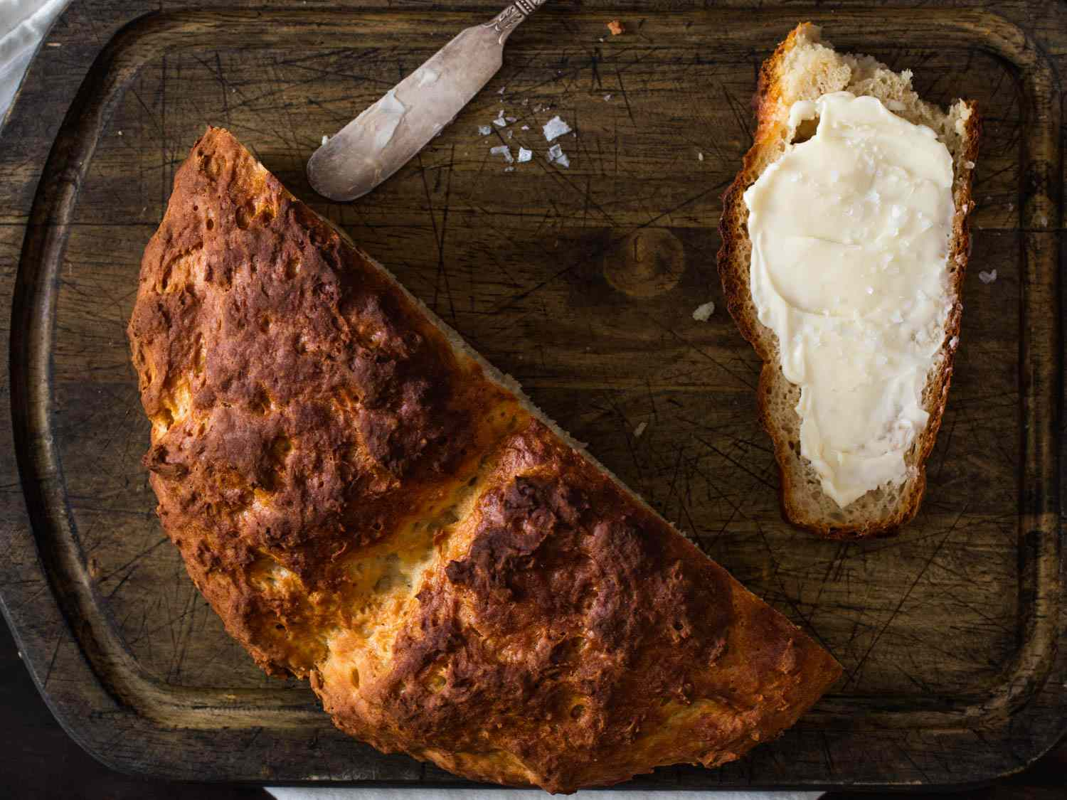 A half loaf of Irish soda bread with a buttered slice next to it on a dark wood cutting board.