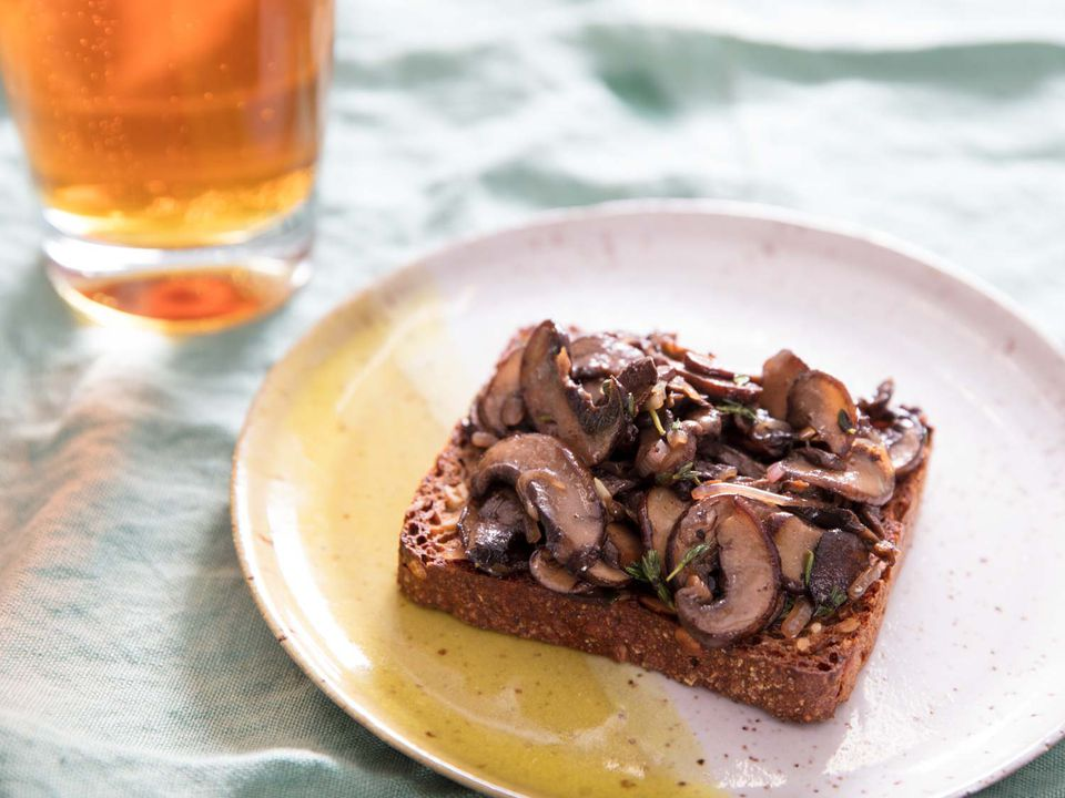 A slice of Danish rye bread toast topped with sautéed mushrooms, next to a glass of beer