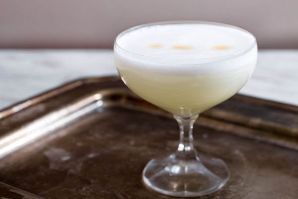 Pisco sour in a cocktail glass on a tray