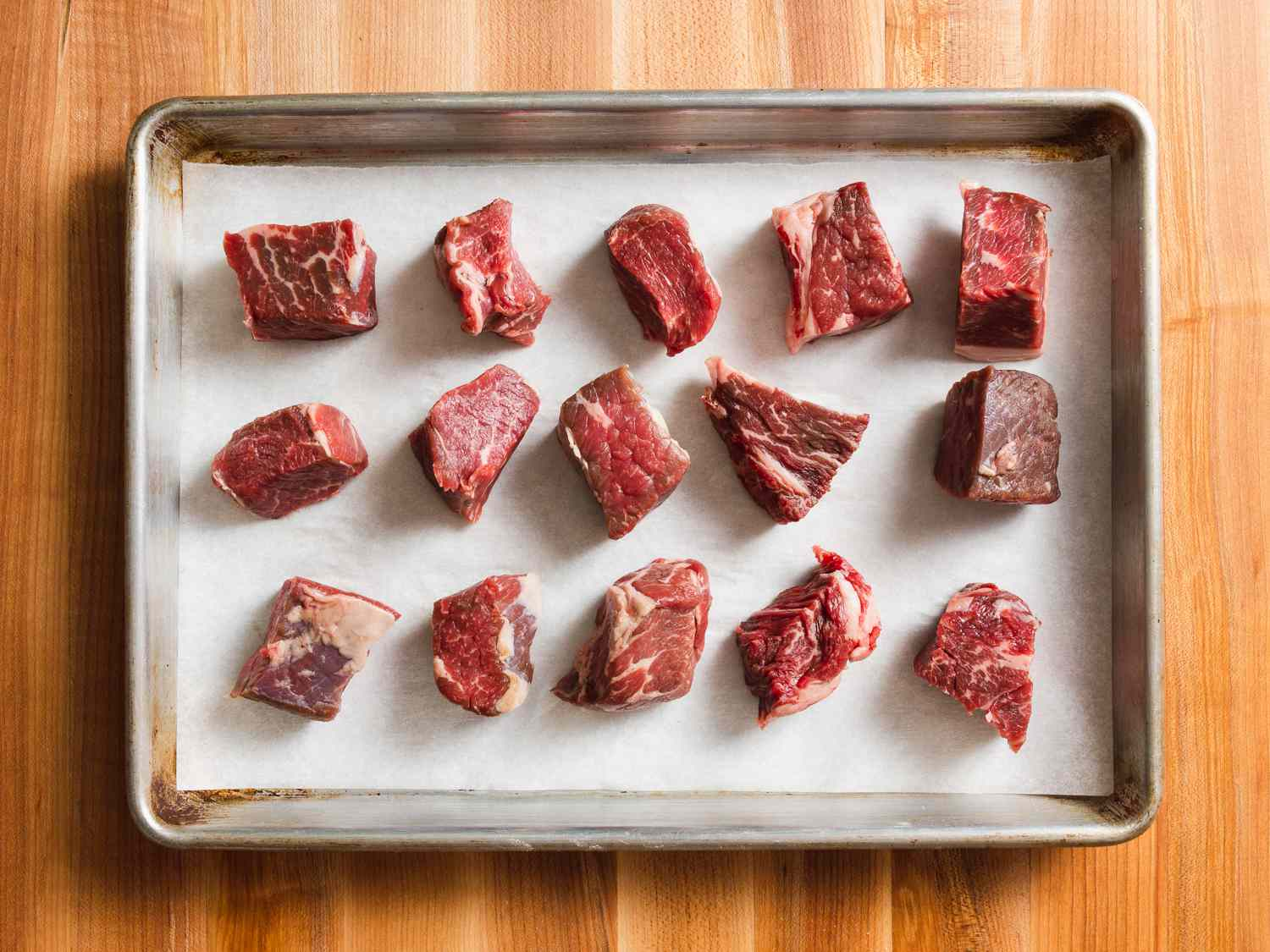 chunks of meat on a parchment-lined baking sheet