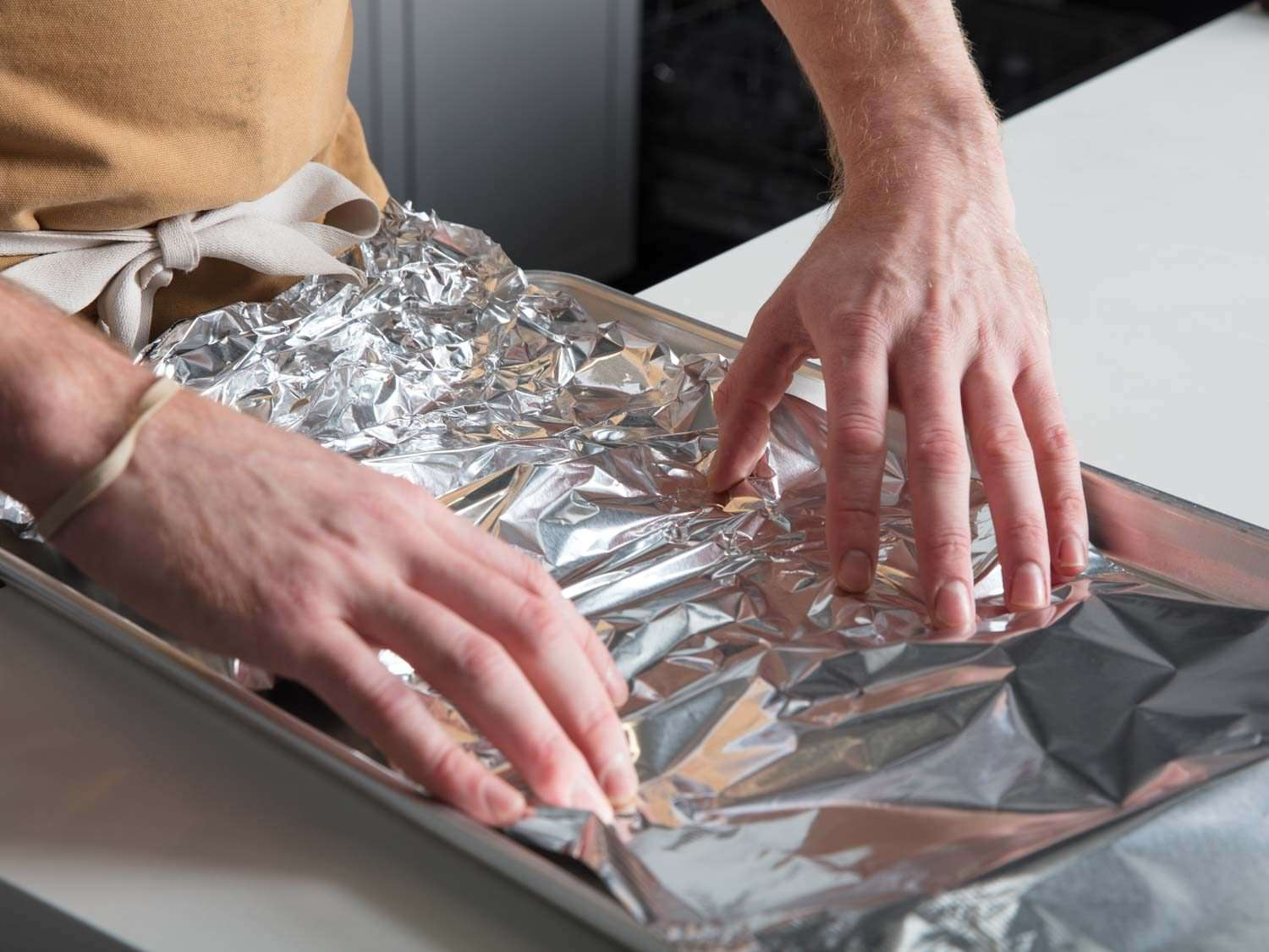 Preparing foil-lined baking sheet for oysters