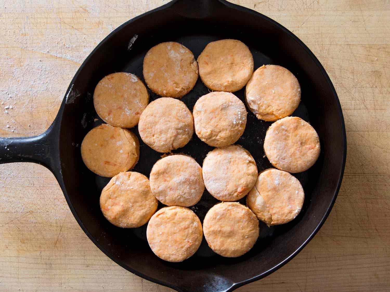 overheat shot of sweet potato dough cutouts arranged inside cast iron skillet