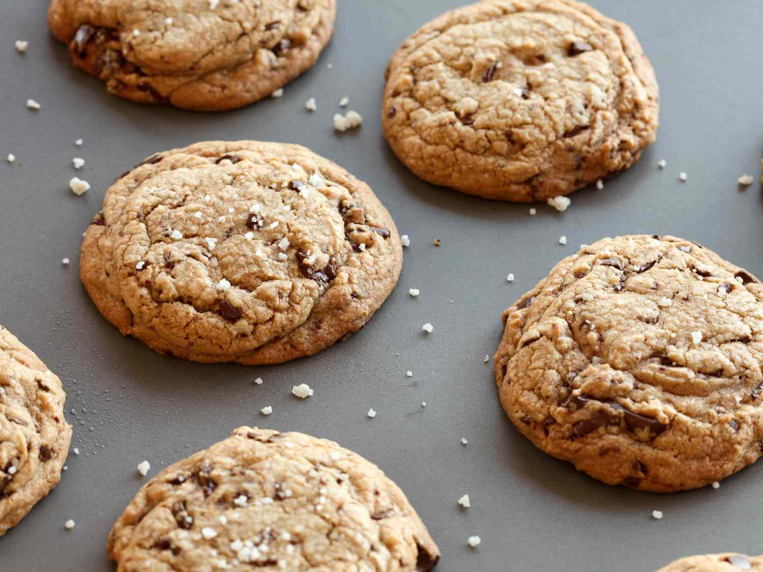 Array of chocolate chip cookies with craggy tops on a grey background.