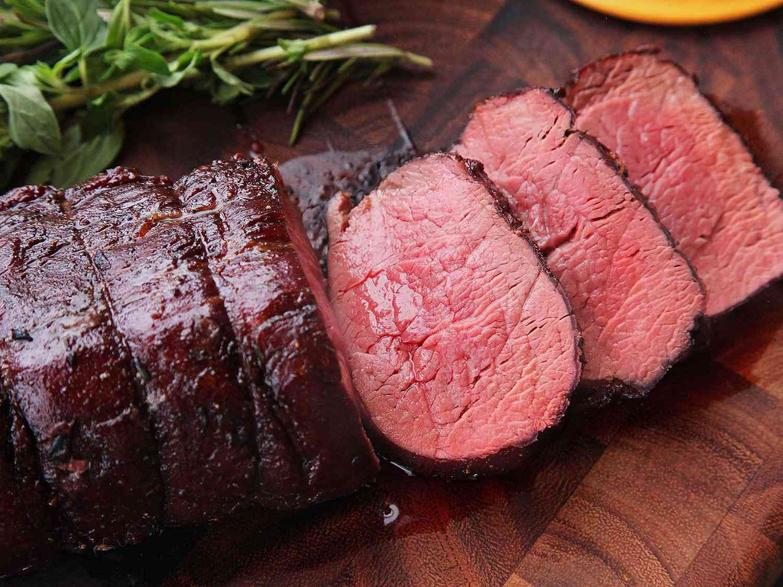 Sliced beef tenderloin on a cutting board.