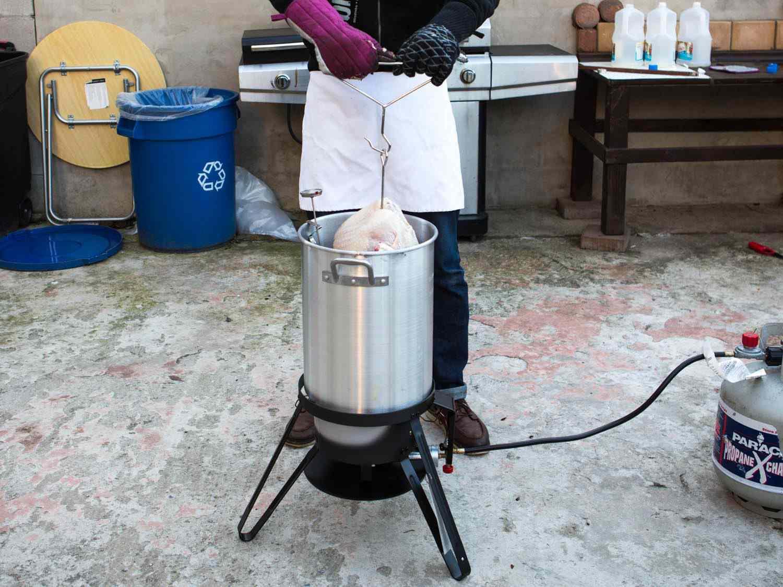 Man lowering turkey into vat of boiling oil