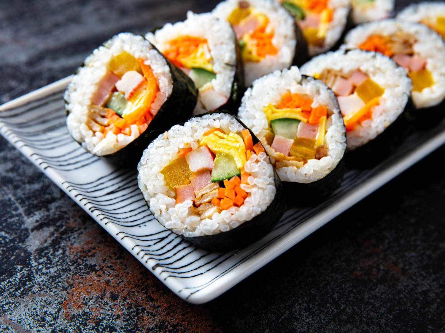 A close up of a small plate of gimbap loaded on it: the rolls look very full of multiple colorful ingredients including bright yellow egg, green cucumber, orange carrot, and more