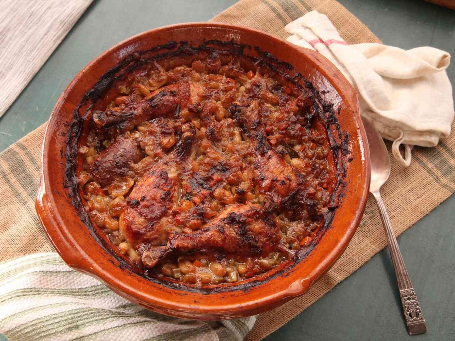 Baked cassoulet in an earthenware pot with a crispy, browned top.