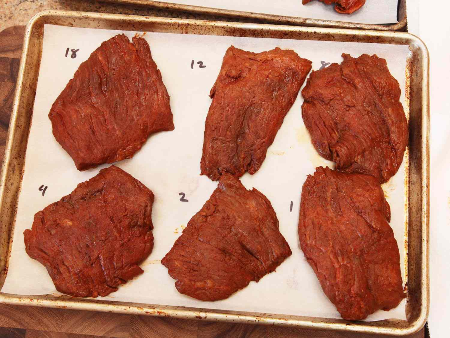 A parchment-lined sheet pan topped with six steaks, each marinated for a different number of hours, before grilling for carne asada.