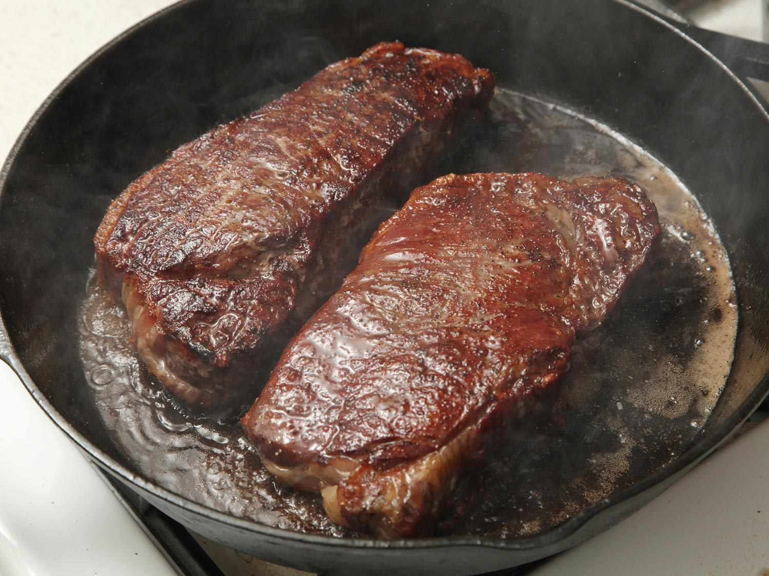 Two thick steaks cooking on a cast-iron skillet with the reverse-sear method
