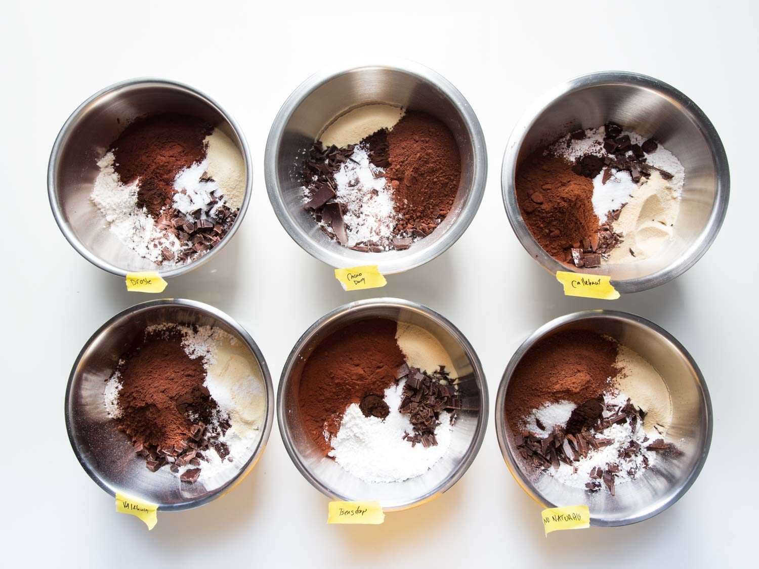 Overhead shot of six bowls containing ingredients for homemade brownie mix, each with a different variety of Dutch cocoa