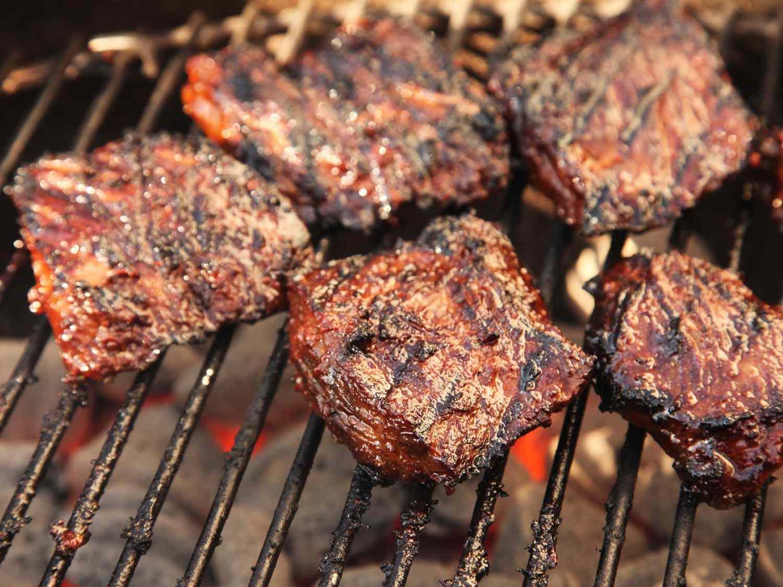 Marinated skirt steaks grilling over charcoal to make carne asada.