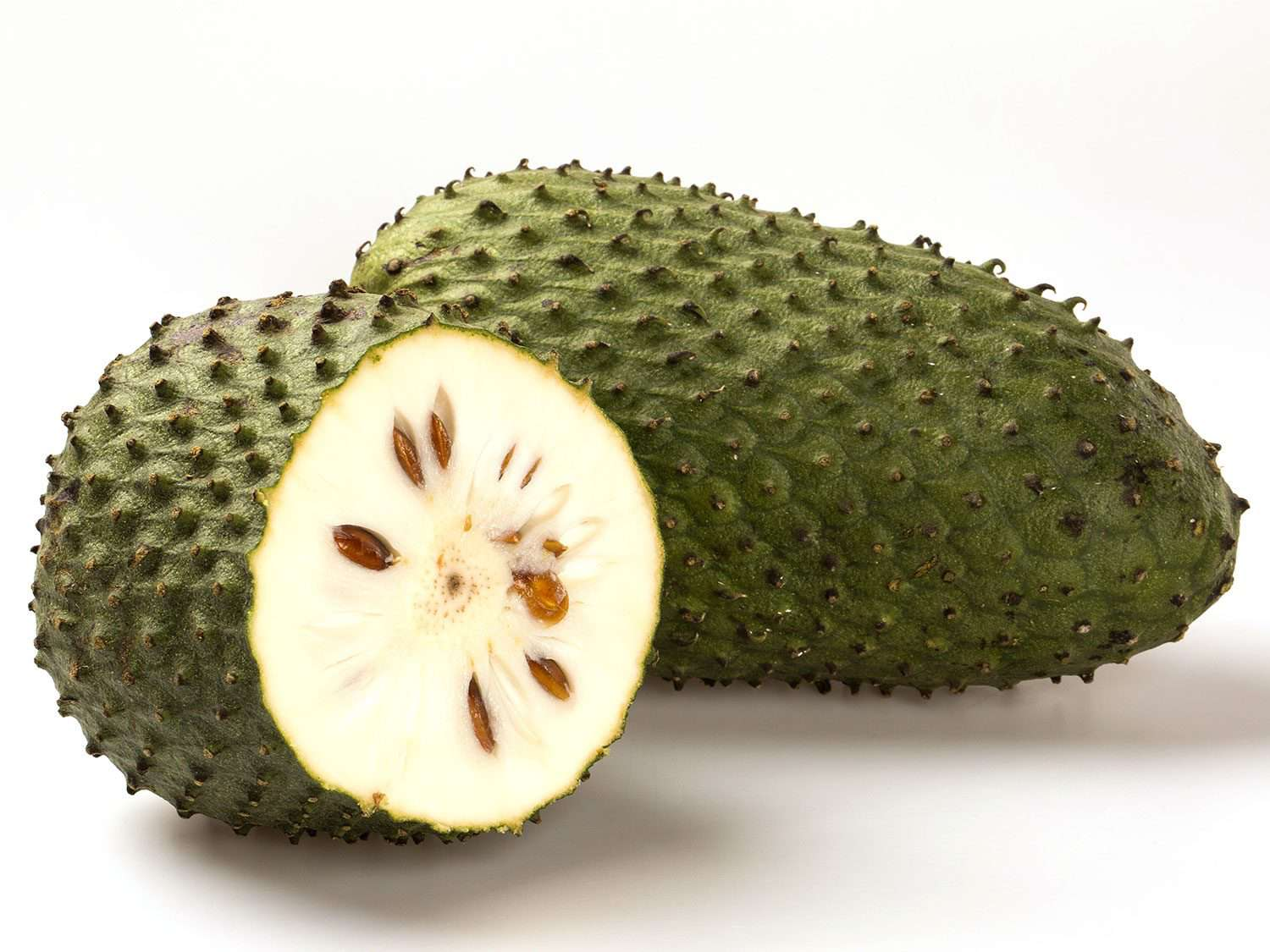 A long whole soursop fruit, with a cut half of another fruit showing the white interior and large dark seeds of the soursop