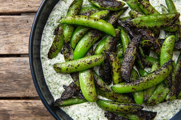 Charcoal Chimney–Grilled Sugar Snap Peas in a bowl on top of Buttermilk-Dill Dressing
