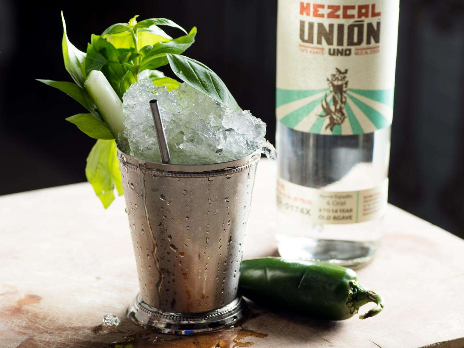 El Derby Ahumado (basil julep with mezcal, cucumber, jalapeño, and fresh basil) in a julep cup, next to a bottle of mezcal