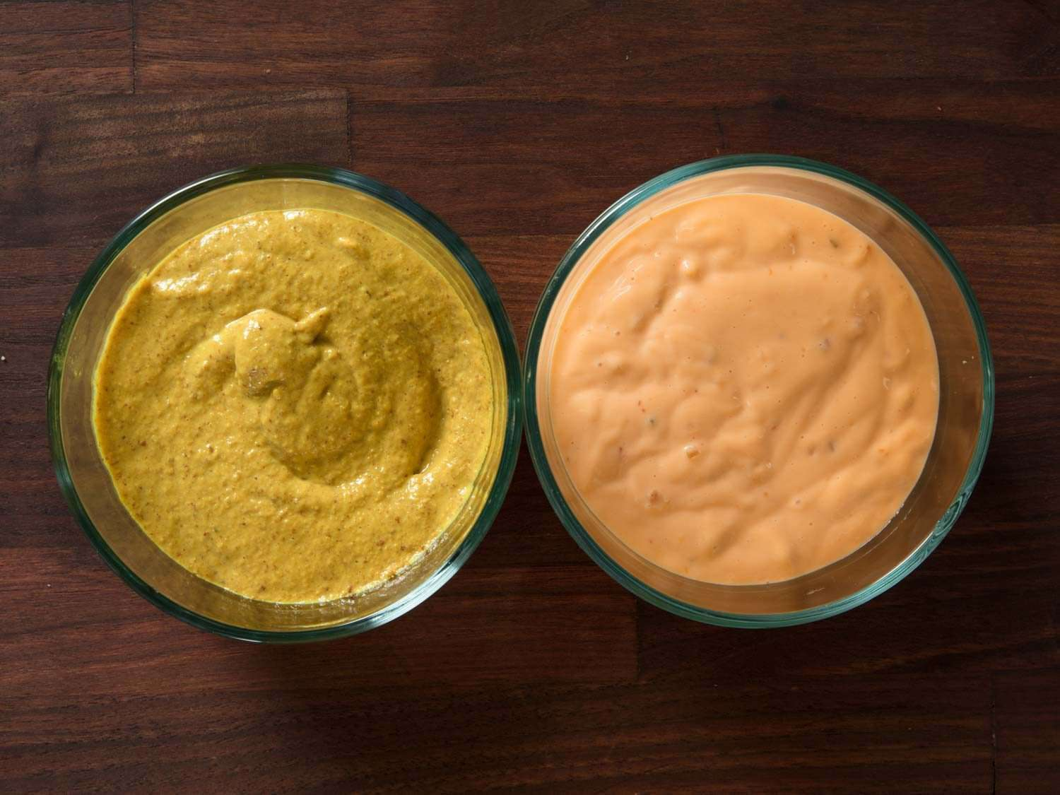 Yellow mustard and Russian dressing in two bowls