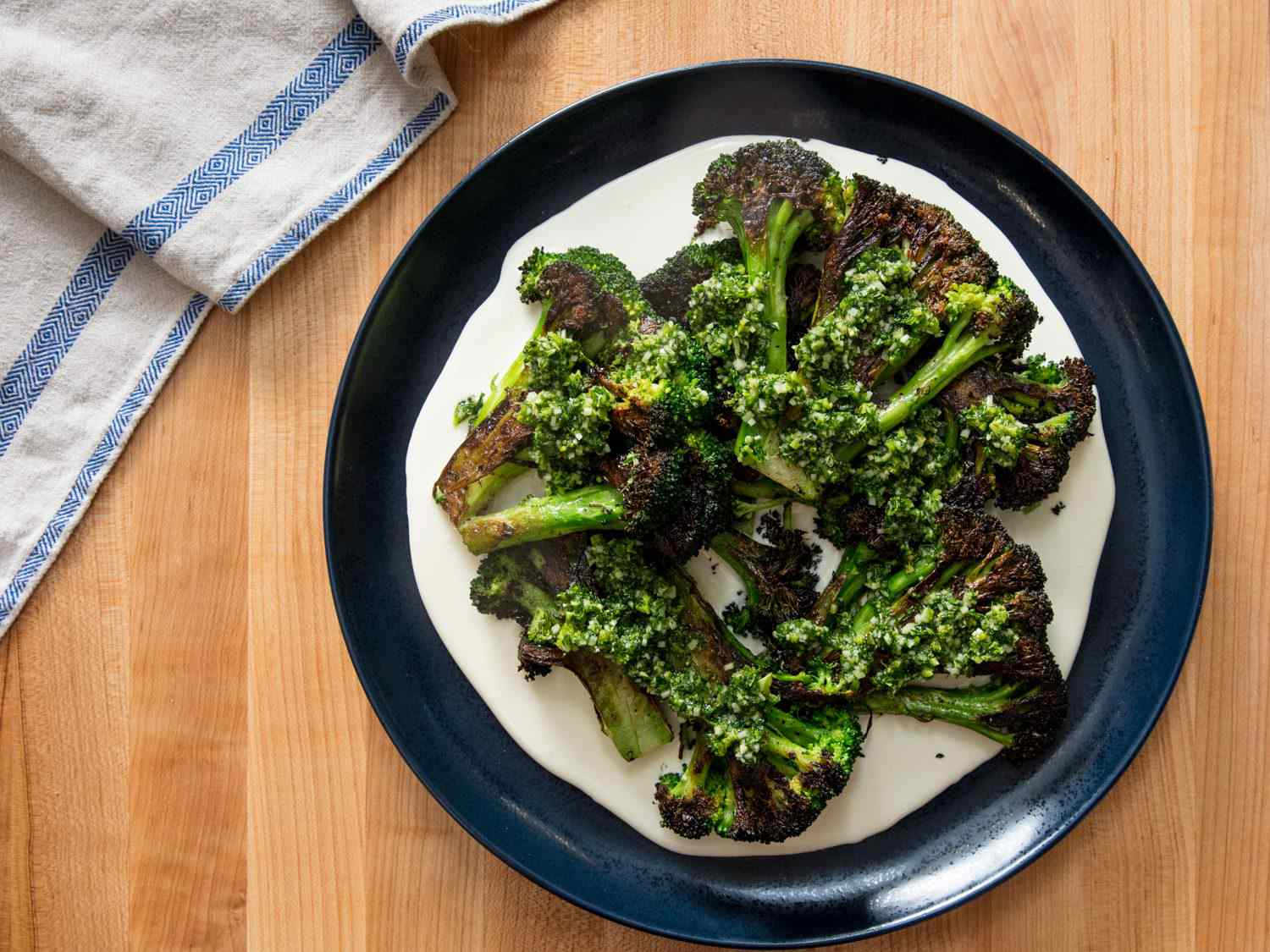 Overhead shot of serving platter with charred broccoli on top of cheese sauce with gremolata.