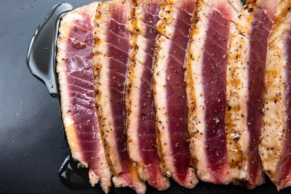 Sliced grilled tuna, cooked rare, on a black plate, seasoned with salt and freshly ground black pepper and drizzled with olive oil.