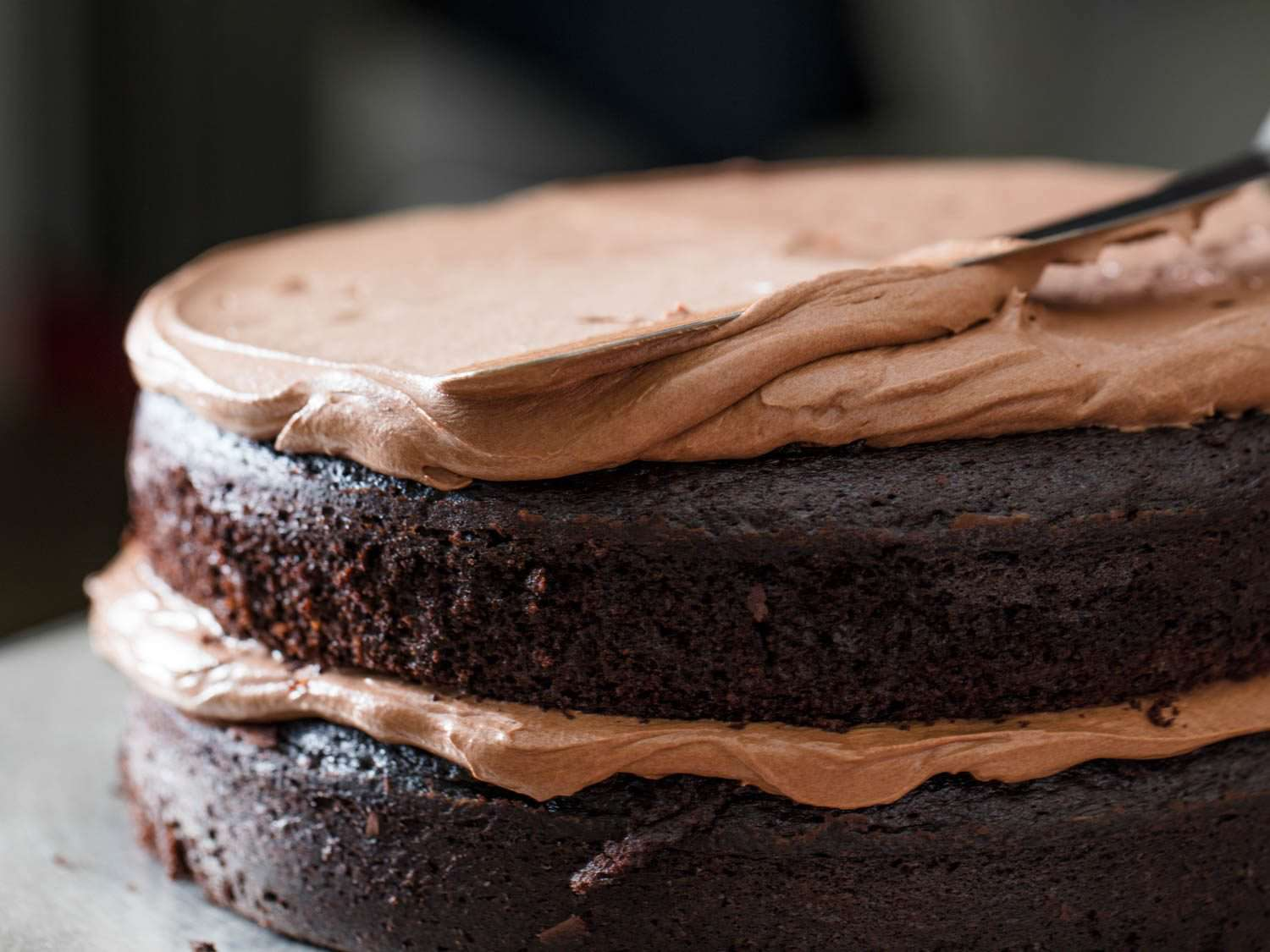 Frosting the second layer of Devil's food cake with chocolate Swiss buttercream.