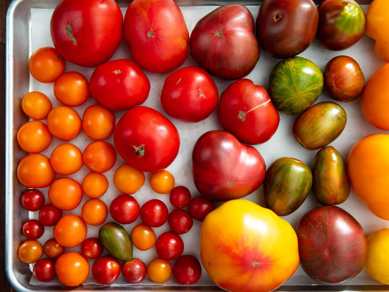 Overhead view of a tray of whole tomatoes of different sizes and colors.
