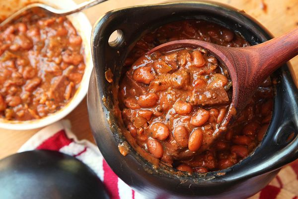 Barbecue beans in a pot, with a bowl of barbecue beans on the side.
