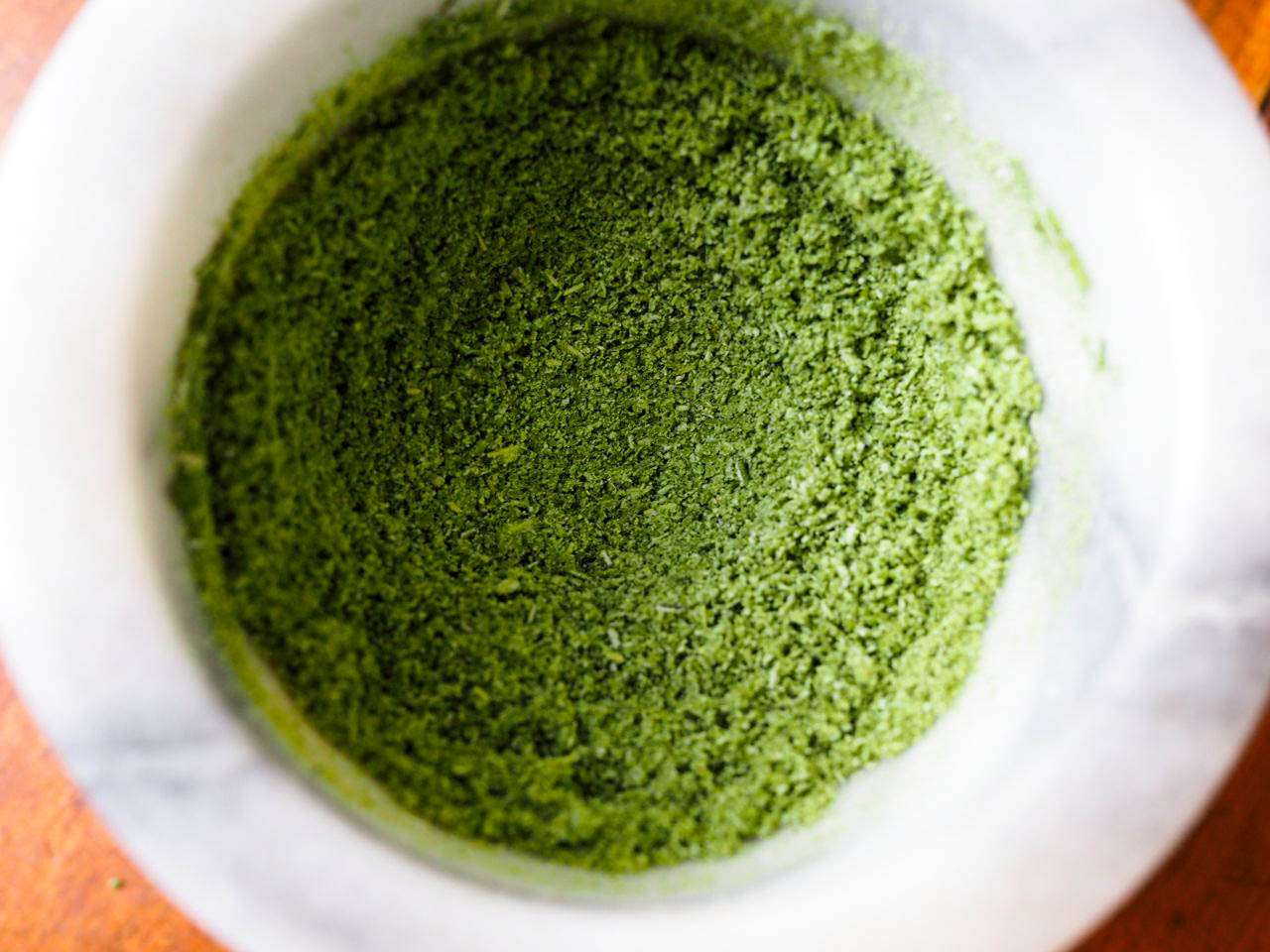 Rosemary leaves that have been dried in the microwave and ground into a bright green powder with a mortar and pestle.