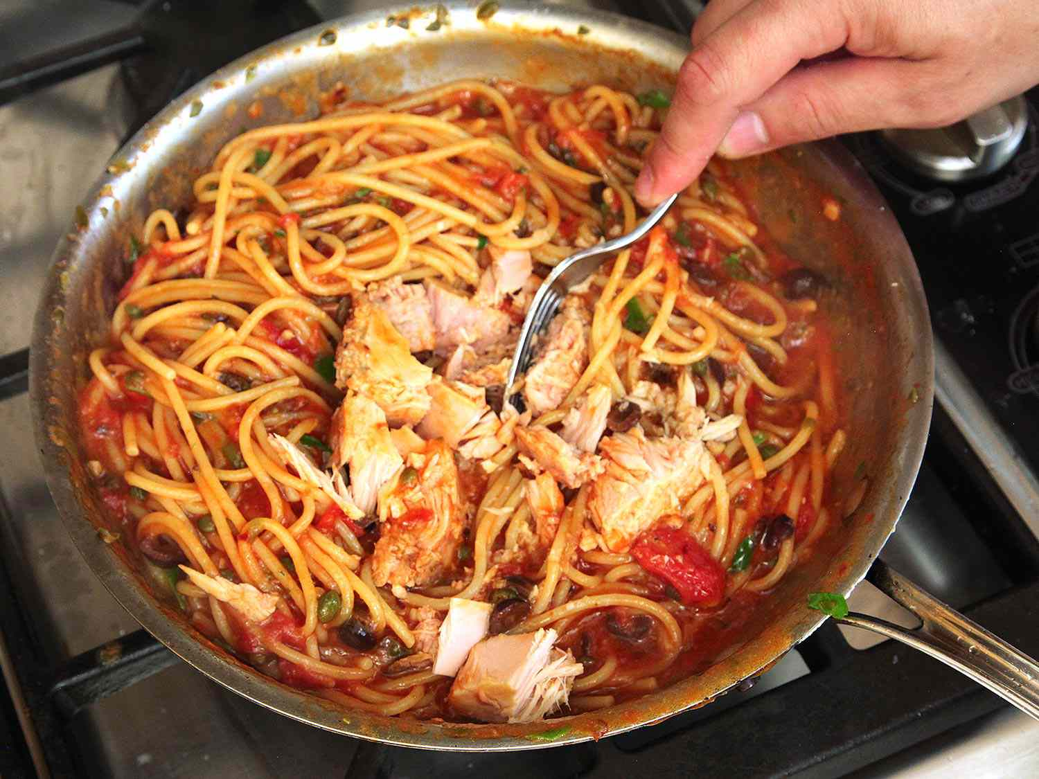 Adding canned tuna to a skillet of pasta puttanesca.
