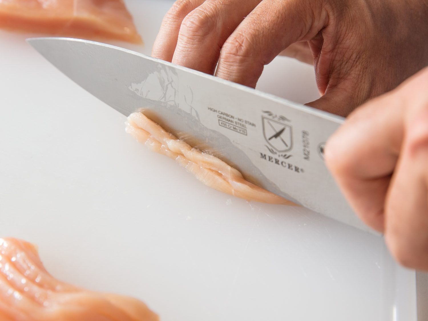 A knife slicing through two slices of chicken breast stacked on top of one another to create julienned strips for stir-frying
