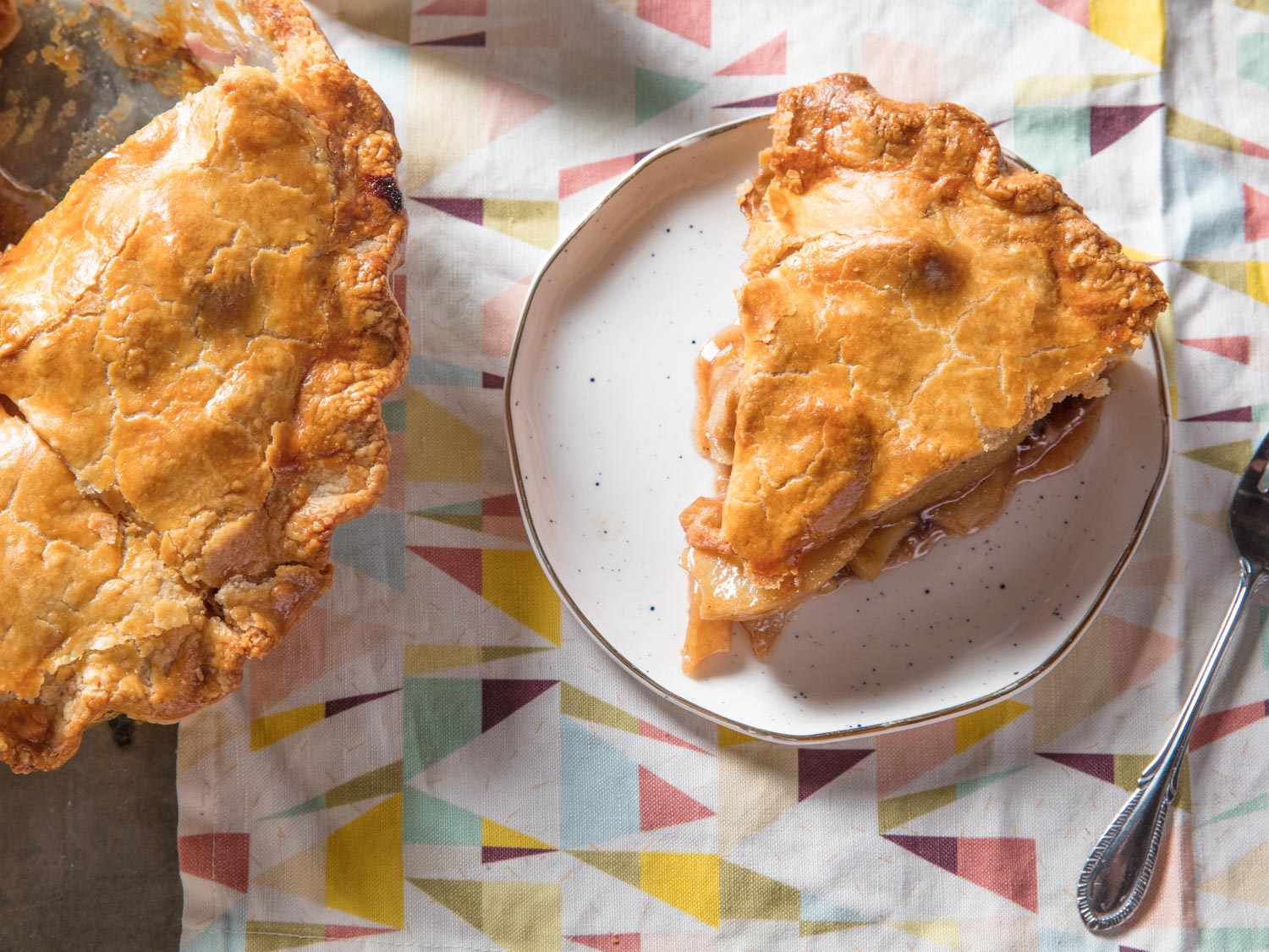 A wedge of apple pie on a plate, next to the rest of the pie