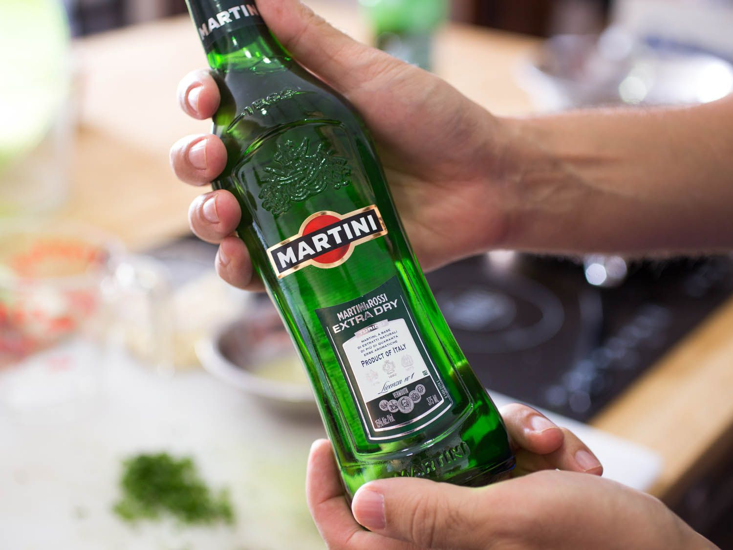 A hand holding up a green bottle of Martini & Rossi extra-dry vermouth