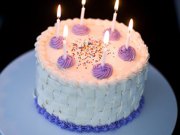 Vanilla cake with sprinkles, decorative purple icing, and lit candles
