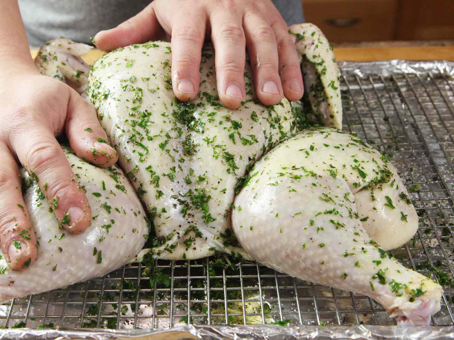 Spreading herbs on the skin of a raw spatchcocked chicken before roasting.
