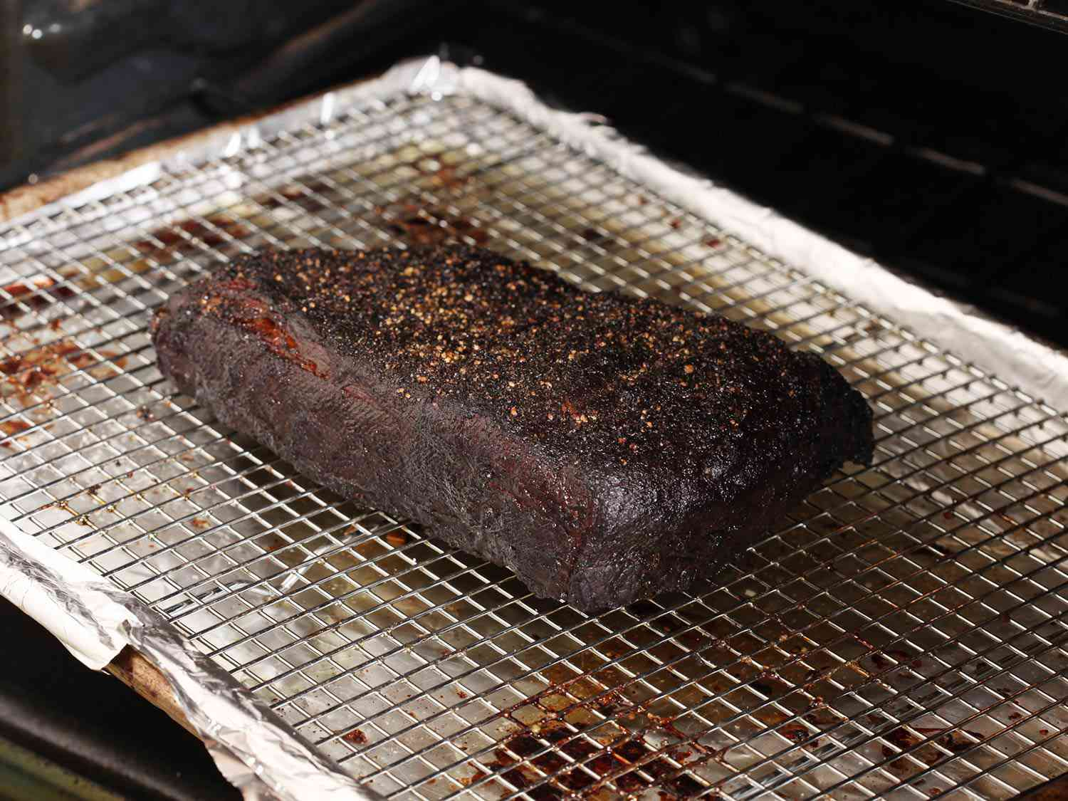 Finished brisket that's been cooked sous vide and then cooked low and slow in the oven, on a wire rack over a foil-lined baking sheet