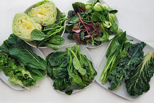 An assortment of different varieties of Chinese greens on five white plates.