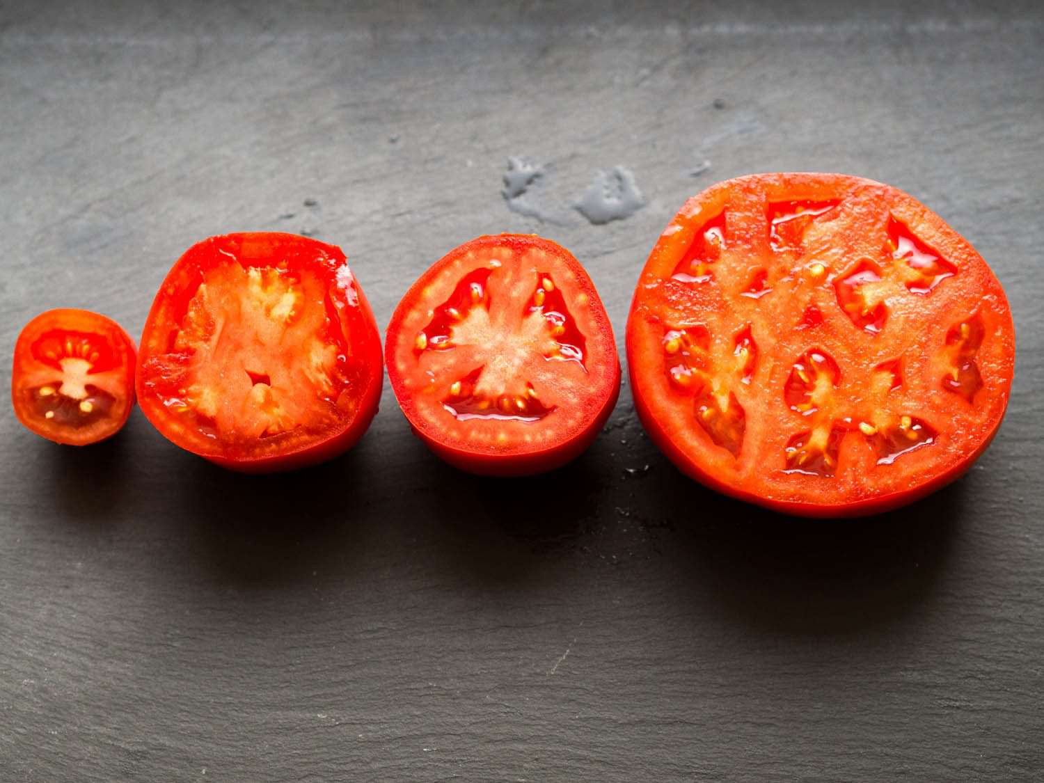 Different varieties of tomatoes cut in half, cut sides facing up