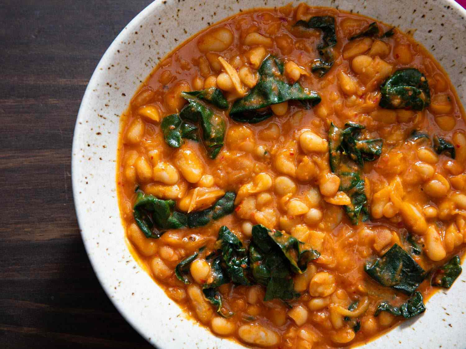 Closeup overhead of a bowl of white bean and kale stew with 'nduja.