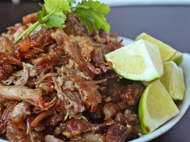 Bowl of braised and crisped carnitas topped with lime wedges and cilantro.