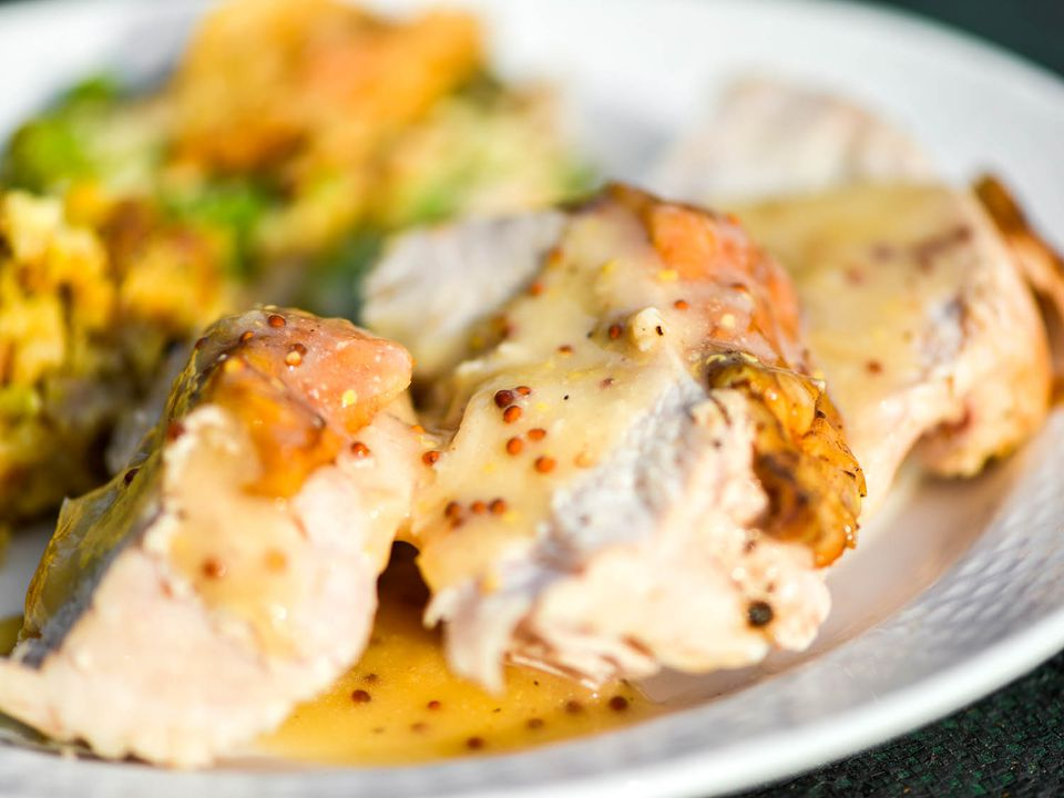 A plate of sliced roasted turkey, drizzled with white wine and mustard gravy.