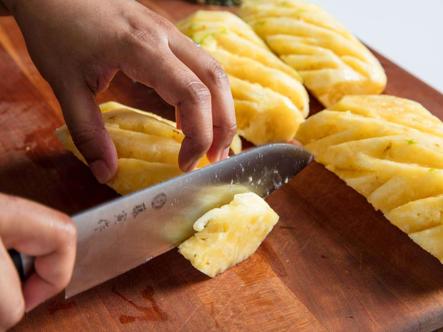 A knife cutting slices of a pineapple.